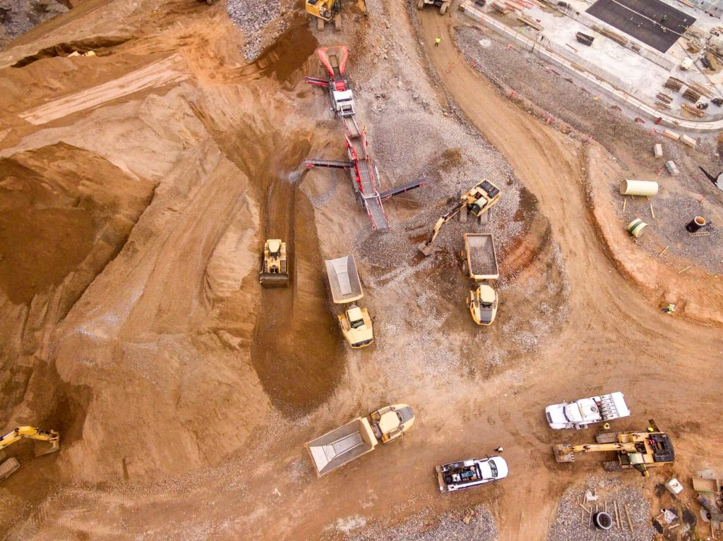 Aerial shot of several mining trucks parked near an open pit mine